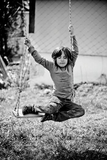 Full length of boy enjoying swing at playground