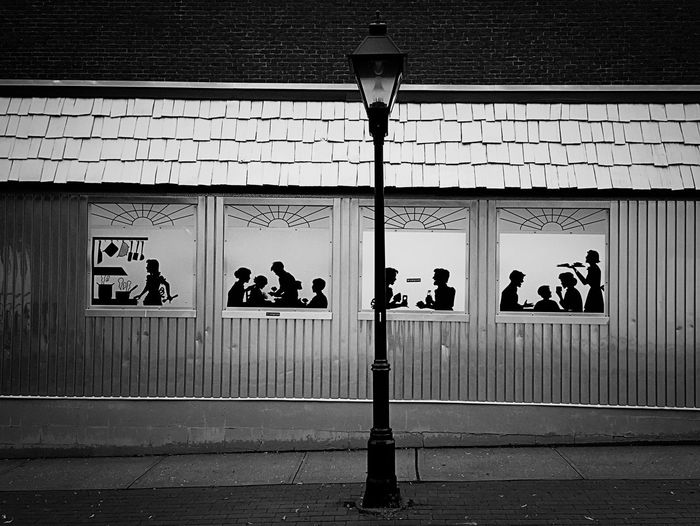 welcome to the cafe of shadows, come in - it's busy..... Built Structure Communication Door Dream Cafe Dream Restaurant Dreamcafe Entrance Lighting Equipment Peek Peering In Railing Shadow Shadow Play Shadowpeople Sidewalk Sign Silhouette Silhouettes Street Light Surreal Surrealism Wall Wall - Building Feature Wall Art Window