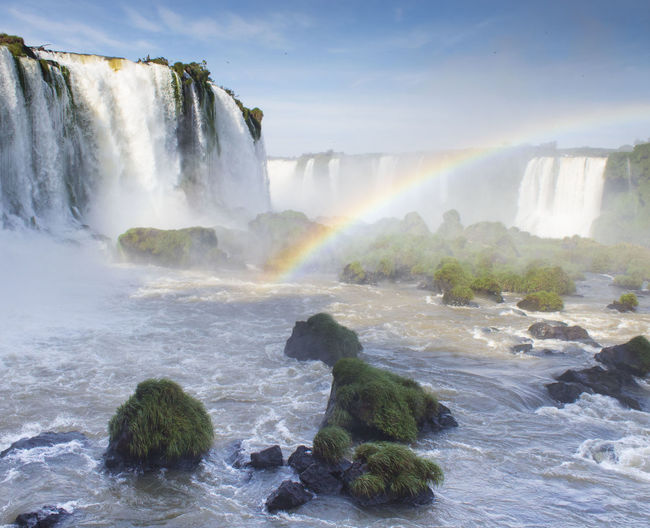 Scenic view of waterfall with rainbow