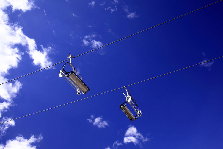 Empty ski lifts in the blue sky Ski Lift Blue Cable Cloud - Sky Day Hanging Low Angle View Nature No People Outdoors Ski Sky