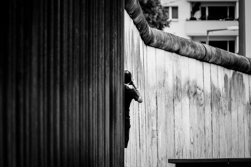 Person by surrounding wall in city