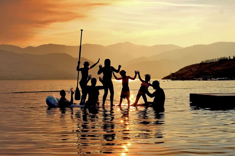 Silhouette people enjoying in lake against mountains