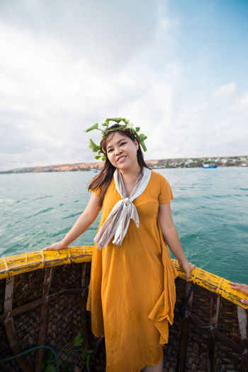 Portrait of smiling woman standing in boat against cloudy sky