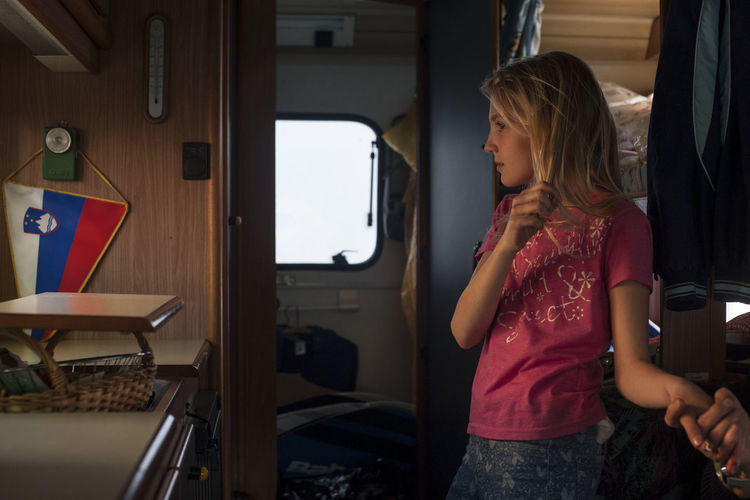 Cropped image of woman holding girl hand standing in motor home