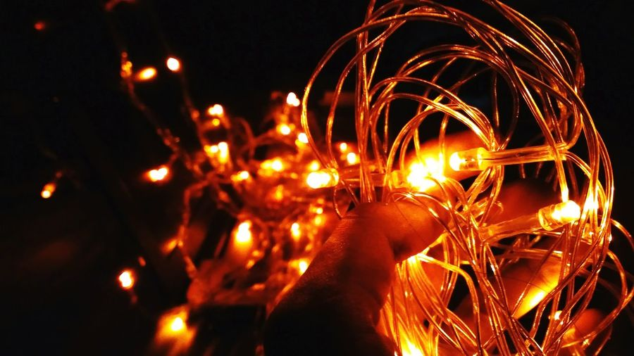 Cropped Hand Holding Illuminated String Light At Night