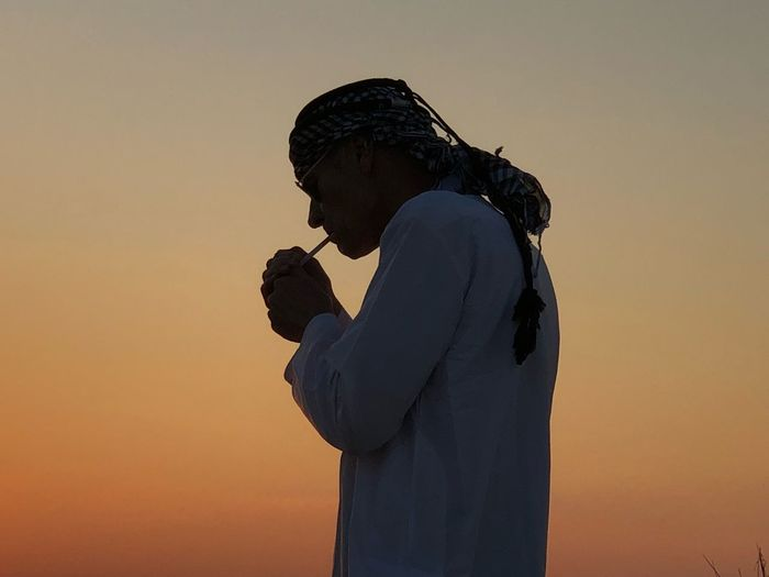 Side view of mature man smoking cigarette against clear sky during sunset