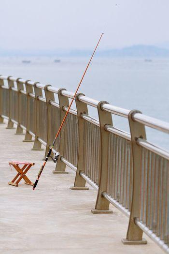 Close-up of fishing rod against railing