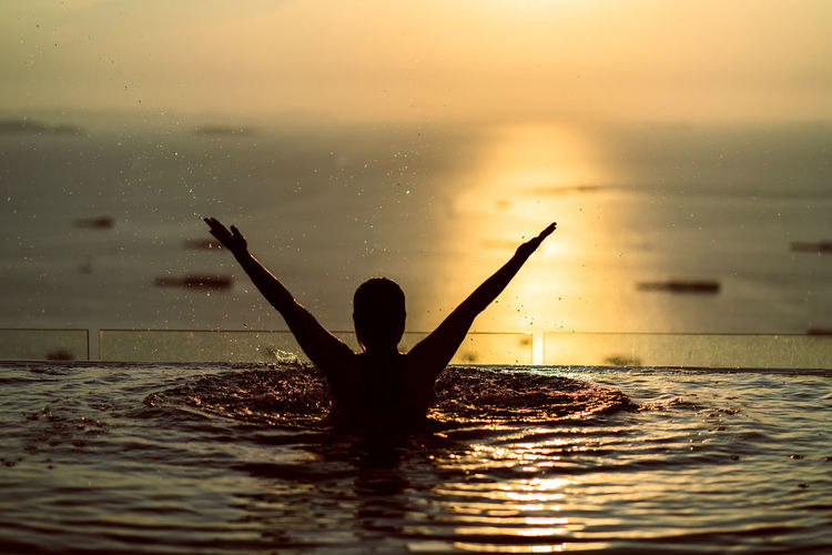 Rear view of silhouette woman in infinity pool with arms raised against sea during sunset