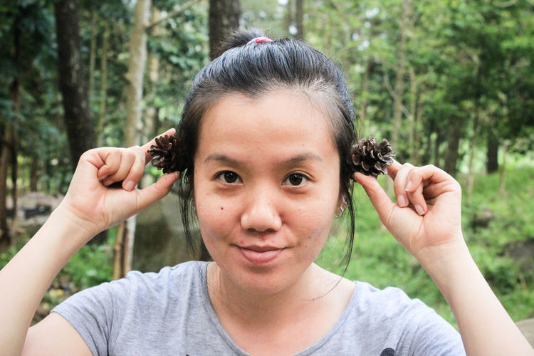 Portrait of smiling woman holding pine cones against trees