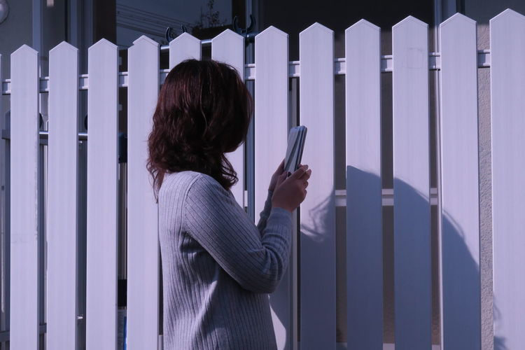 Side view of woman using phone by fence