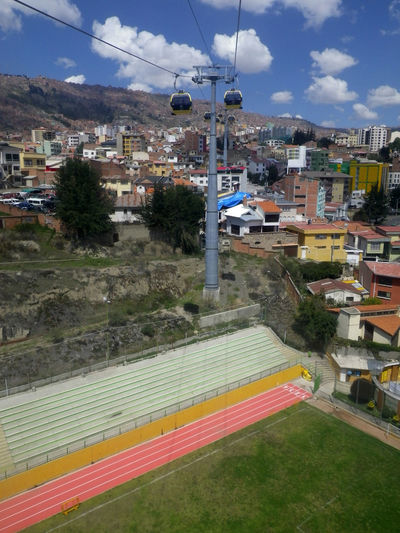 """View from """"Mi Teleferico"""" (cable car) in La Paz, Bolivia. Cable Car Cityscape Colourful Grass Teleferico Architecture Athletics Track Building Exterior Built Structure Cable Clouds Day Footballfield Mountain Nature No People Outdoors Road Sky Soccer Field Transportation Tree"""