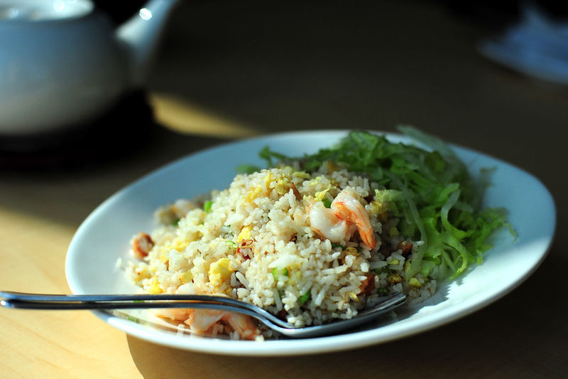High angle view of rice with salad served in plate on table