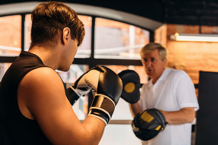 Coach boxing with boxer in  ring