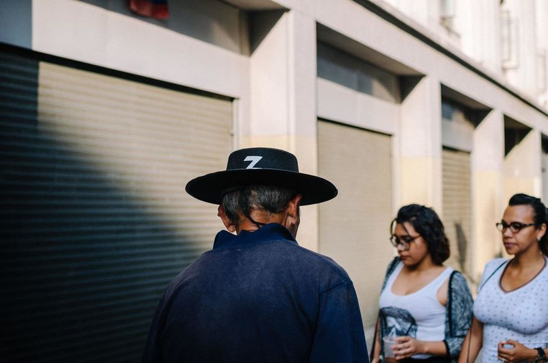Sad Zorro Men Real People Hat Headshot Architecture Built Structure Portrait Clothing Lifestyles Group Of People Building Exterior Day Casual Clothing Standing People Focus On Foreground Leisure Activity Front View Adult Young Adult Outdoors Hairstyle Streetphotography Street Photography EyeEm Best Shots EyeEm Selects The Street Photographer - 2019 EyeEm Awards