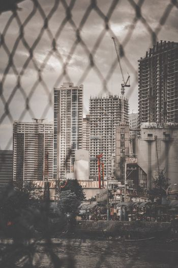 Buildings in city seen through chainlink fence