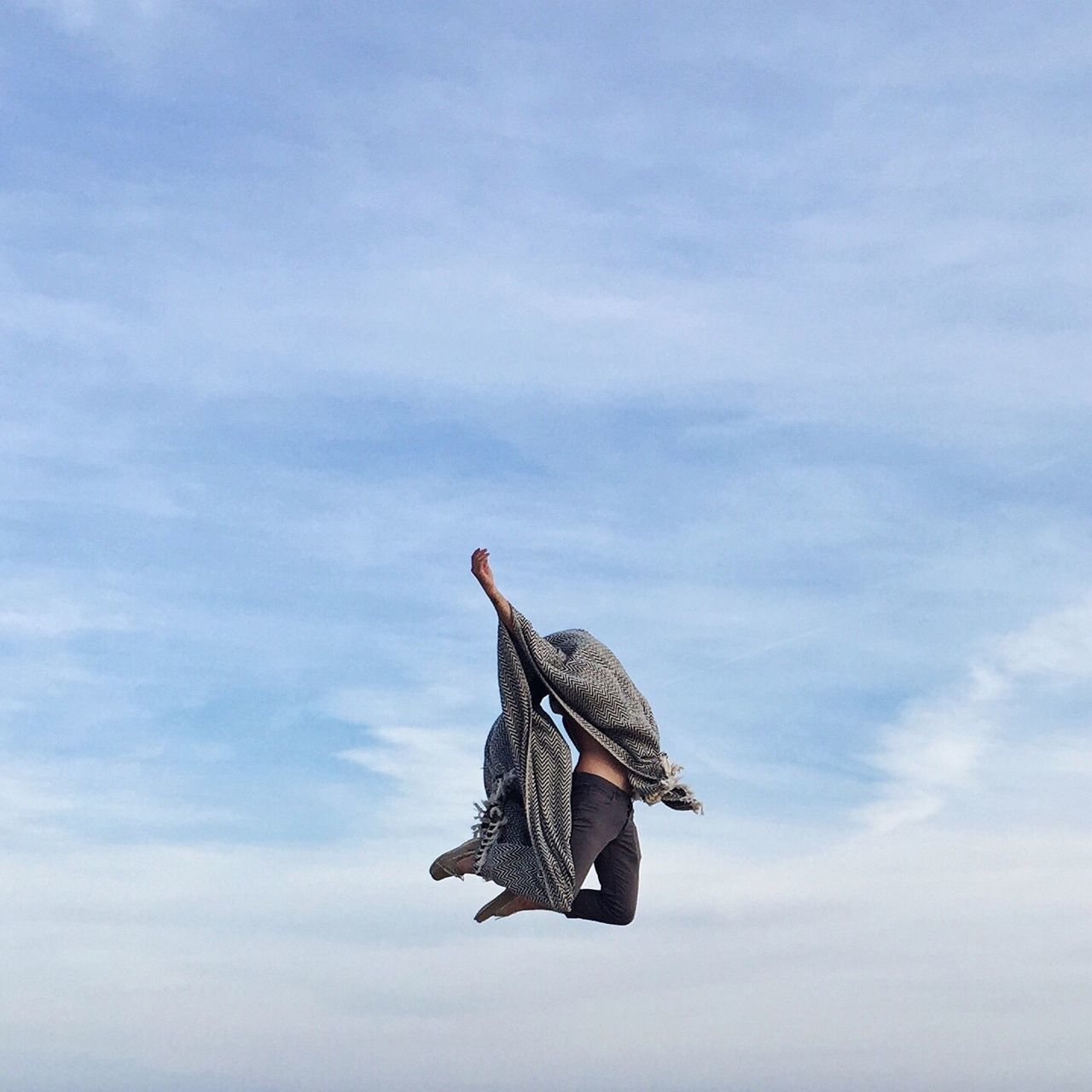 Low Angle View Of Person Covered With Scarf Jumping In Mid-Air Against Cloudy Sky