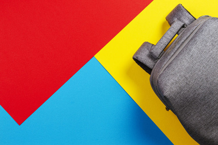 Top view of gray backpack on yellow, blue and red background.