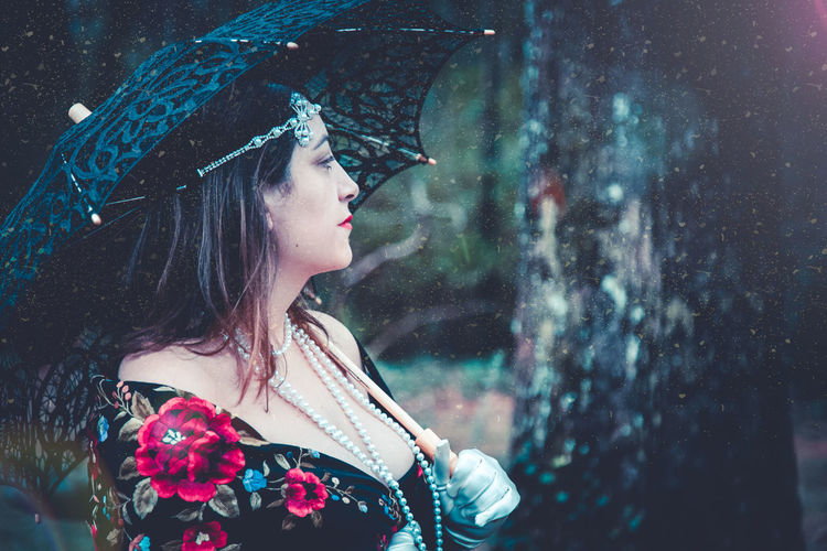 Side view of thoughtful woman wearing pearl necklace with umbrella looking away