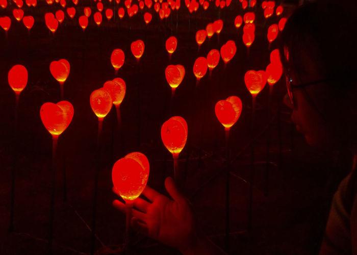 Midsection of woman holding illuminated lantern at night