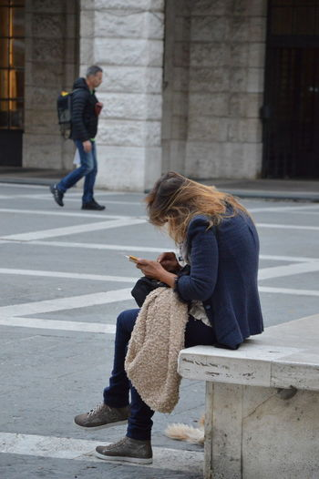 A woman on an square in Italy and takes care of her smartphone A Woman On An Square In Italy And Takes Care Of Her Smartphone Woman City People's Townspeople Lifestyles Citizen City Dweller Town Dweller Smartphone Empty Square Two People Street People City Life City Italy Alone Cityscape
