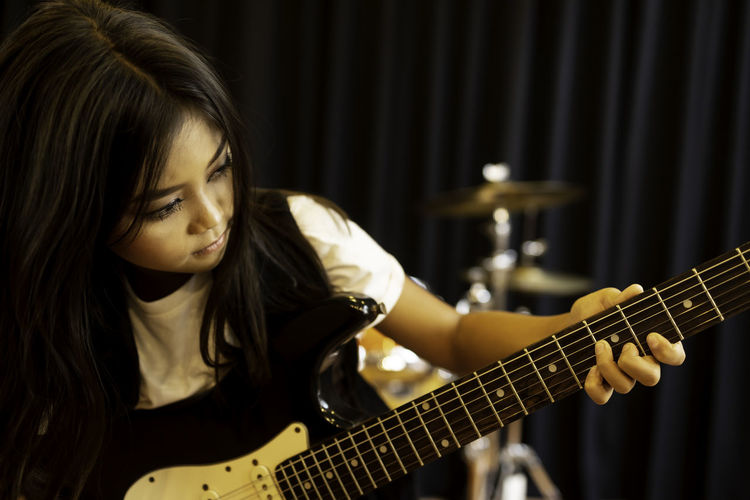 Girl with long hair playing guitar