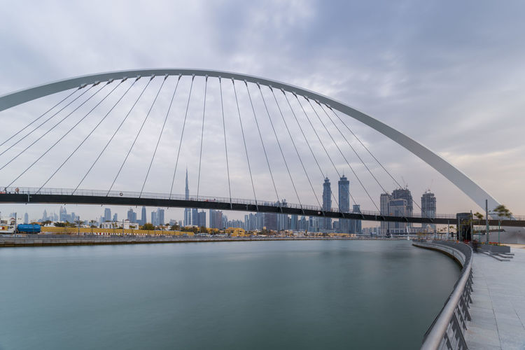 View of bridge over river against sky in city