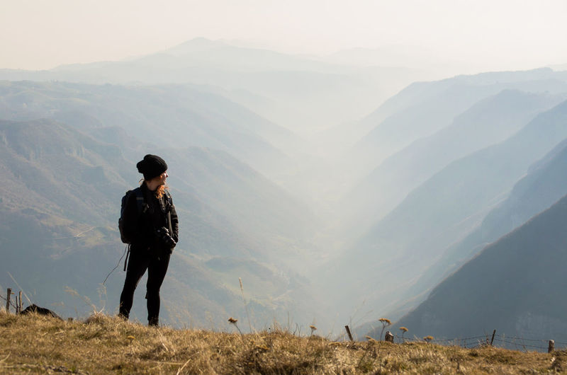 Woman looking at view while standing on mountain