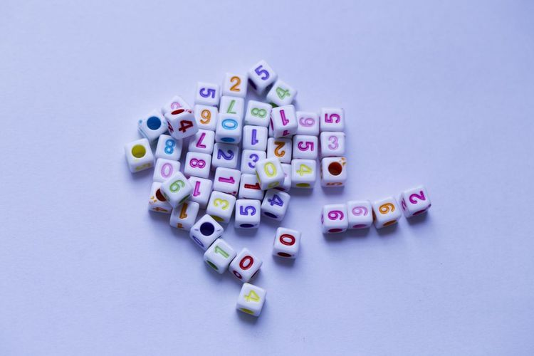 High angle view of numbers on beads over purple background