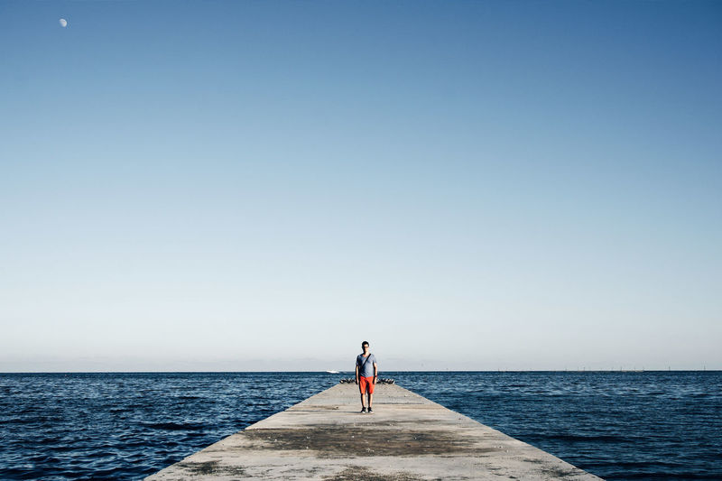 Scenic view of man standing on pier