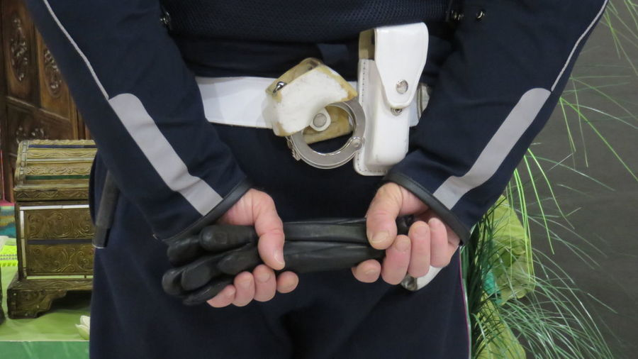 Midsection Of Male Police Officer Holding Protective Glove