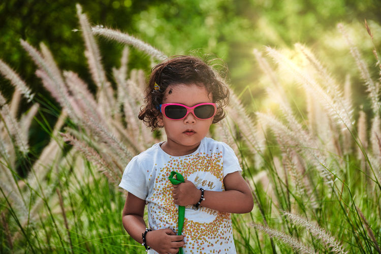 A Kid Casual Clothing Child Childhood Day Fashion Field Front View Glasses Grass Growth Hairstyle Innocence Land Leisure Activity Lifestyles Nature One Person Outdoors Plant Real People Sunglasses