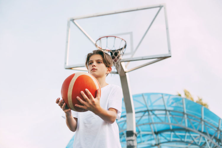 Low angle view of boy playing basketball against clear sky