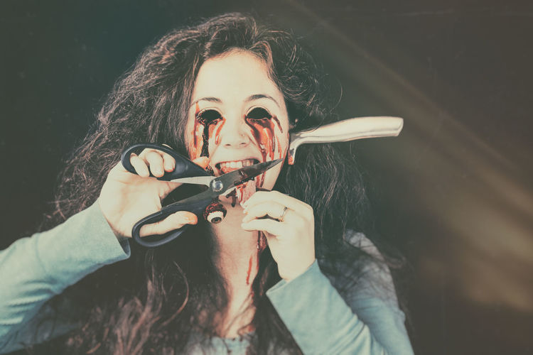 Spooky woman cutting tongue with knife