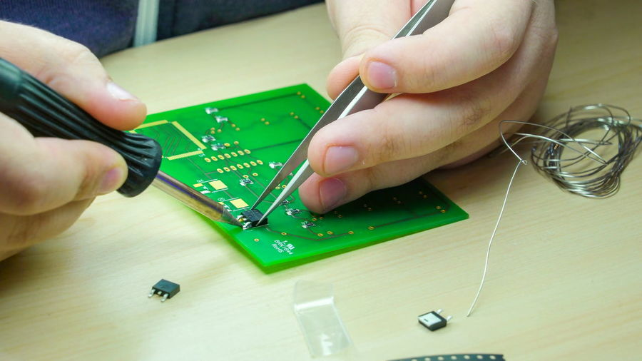 Close-up of person repairing circuit board at table