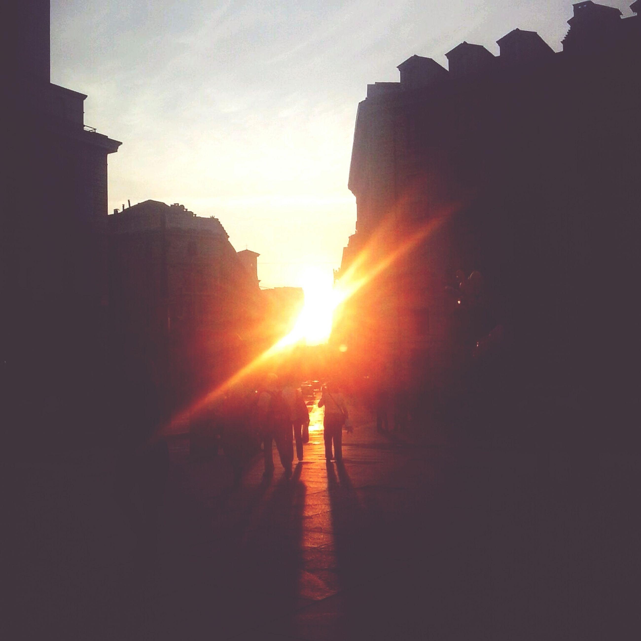 architecture, sunset, built structure, building exterior, silhouette, sun, sunlight, sky, the way forward, sunbeam, city, building, lens flare, orange color, outdoors, walking, unrecognizable person, men, railing