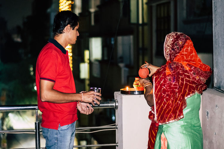 Woman standing with man on terrace during karva chauth at night