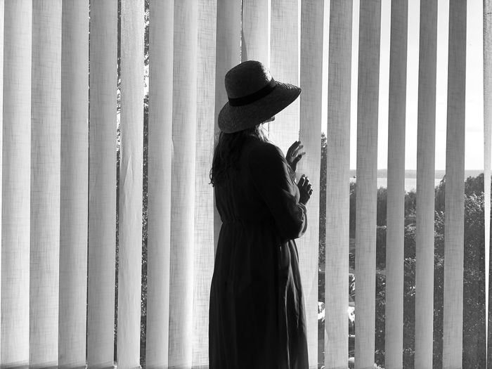 Black and white photo of woman wearing hat standing near the blinds