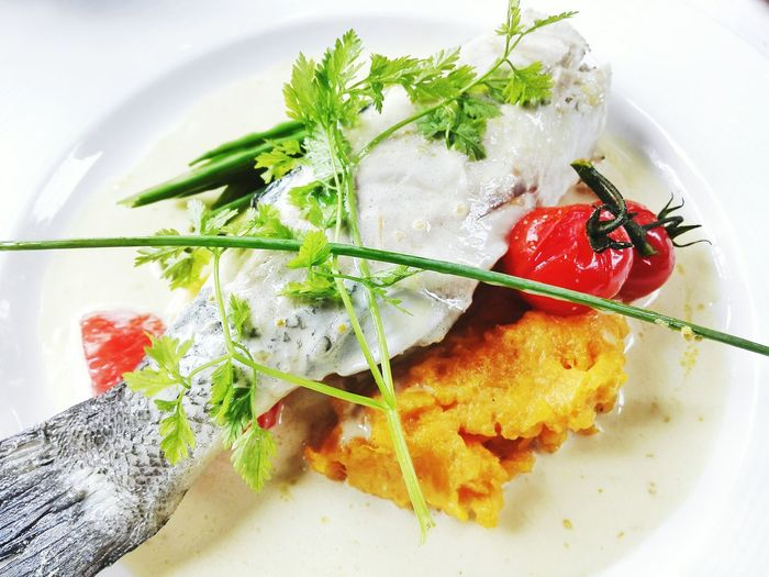 Close-up of fish with vegetables served in plate