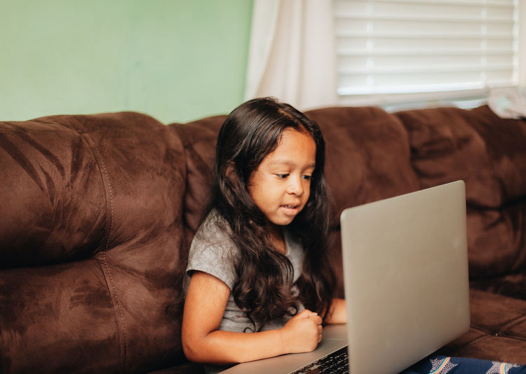 Cute girl using laptop while sitting on sofa at home