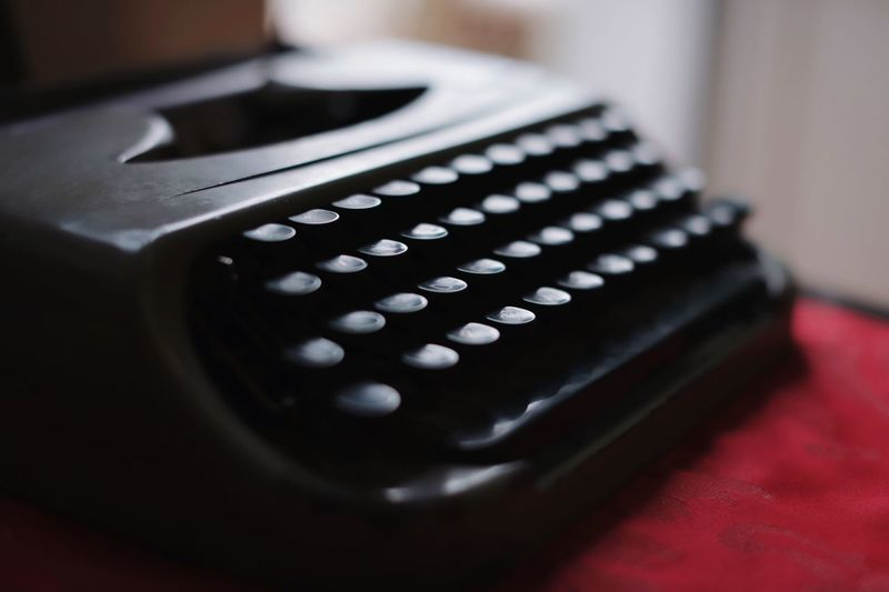 Old typewriter still makes magic happen Interior Design Litterature Writing Cinematic Typewriter Close-up Indoors  Selective Focus Still Life No People Technology Table Arts Culture And Entertainment Focus On Foreground Single Object Photography Themes Communication Number Shape Black Color Machinery Equipment Western Script Circle