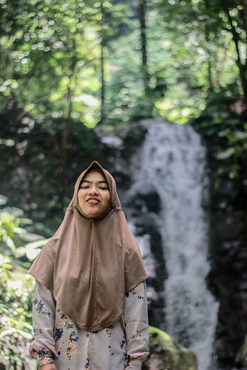 Portrait of smiling young woman wearing hijab standing against waterfall