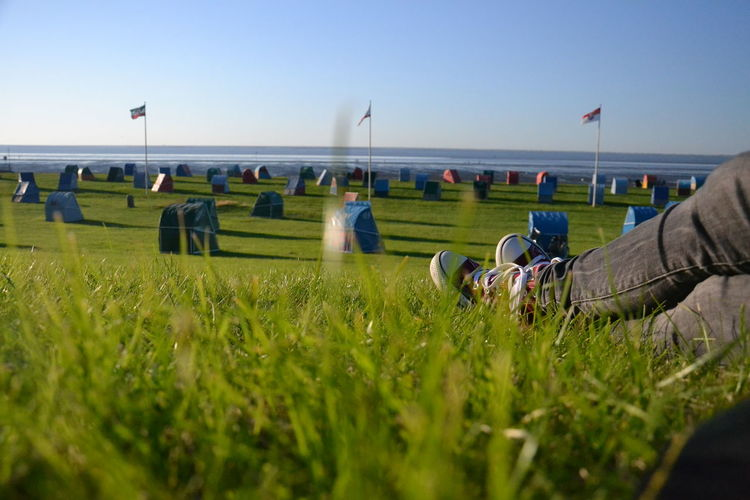 Relaxing at the grassy beach Beach Beach Huts Blue Clear Sky Cuxhaven Feet Field Flags Flags In The Wind  Grass Grassy Green Color Legs Legs_only Leisure Activity Northsea Otterndorf Person Relaxation Sky Sunlight Tranquil Scene Woman First Eyeem Photo