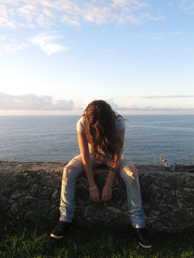 Woman covering face with hair while sitting on retaining wall by sea