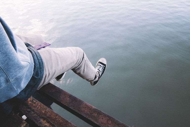 Low Section Of Person Sitting On Pier Over Lake
