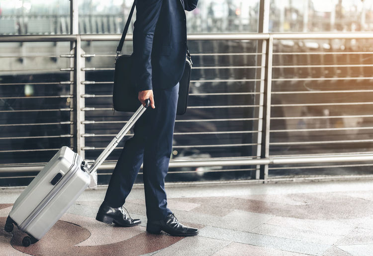 Low section of businessman with suitcase standing in airport