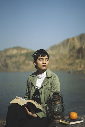 Young woman looking away while holding book sitting by lake
