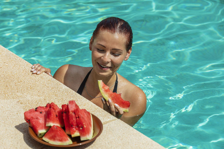 Young woman eating watermelon in the pool Water Swimming Pool Pool One Person Wellbeing Food Food And Drink Leisure Activity Nature Outdoors Watermelon Eating Plate Healthy Lifestyle Women Adult Smiling Young Adult Summer Relaxation Lifestyles Headshot Beautiful Woman Mallorca Mediterranean