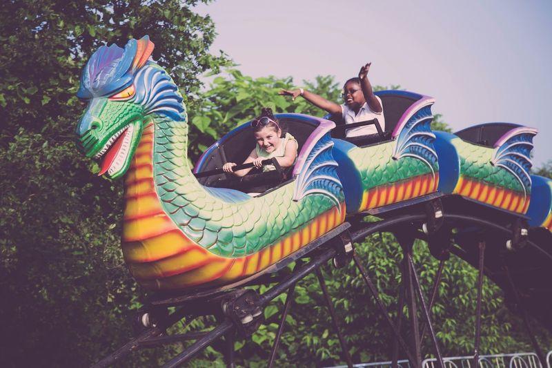 Girls Enjoying Dragon Ride Against Sky