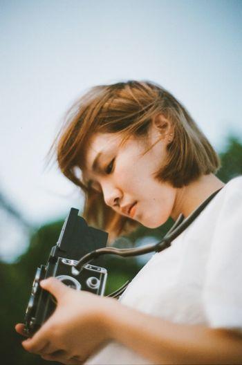 Portrait of teenage girl holding camera against sky