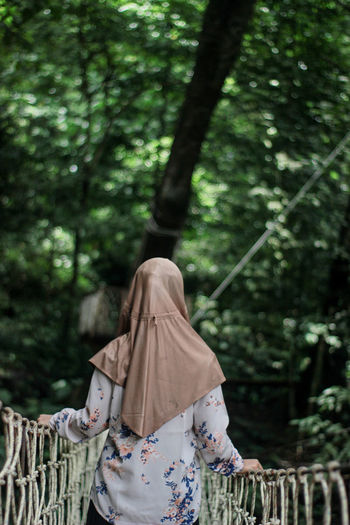 Rear view of woman standing on footbridge against trees in forest